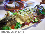 Купить «Stuffed pike with lemon slices on the table», фото № 25841418, снято 18 июля 2015 г. (c) Losevsky Pavel / Фотобанк Лори