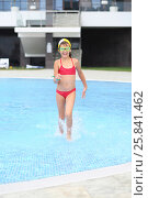 Купить «A girl in a red swimsuit swimming cap and goggles runs out of pool», фото № 25841462, снято 27 июля 2014 г. (c) Losevsky Pavel / Фотобанк Лори