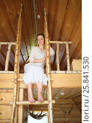 Купить «Barefoot beautiful woman is sitting on top of a wooden staircase in a wooden house», фото № 25841530, снято 19 июля 2015 г. (c) Losevsky Pavel / Фотобанк Лори