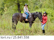 Купить «Woman in red jacket holds by the bridle horse on whom her daughter sits. Both in cowboy hats.», фото № 25841558, снято 13 сентября 2015 г. (c) Losevsky Pavel / Фотобанк Лори