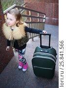 Купить «Pretty little girl standing with a large green suitcase on stairs», фото № 25841566, снято 17 апреля 2014 г. (c) Losevsky Pavel / Фотобанк Лори