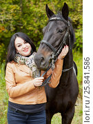 Купить «Smiling black-haired woman stands with horse in park», фото № 25841586, снято 13 сентября 2015 г. (c) Losevsky Pavel / Фотобанк Лори