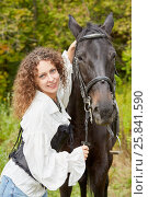Купить «Smiling woman with curly hair stands with bay horse in the park», фото № 25841590, снято 13 сентября 2015 г. (c) Losevsky Pavel / Фотобанк Лори