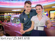 Купить «Young man and woman in retro dress at the bar with pink car», фото № 25841618, снято 18 января 2015 г. (c) Losevsky Pavel / Фотобанк Лори