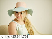 Купить «Portrait of young blond woman in wide-brimmed hat on couch in studio», фото № 25841754, снято 7 марта 2015 г. (c) Losevsky Pavel / Фотобанк Лори