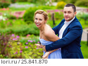Купить «Handsome man in suit and young woman play and laugh in summer garden», фото № 25841870, снято 19 июля 2015 г. (c) Losevsky Pavel / Фотобанк Лори