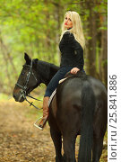 Купить «Blonde beautiful woman in black rides horse in green autumn park», фото № 25841886, снято 13 сентября 2015 г. (c) Losevsky Pavel / Фотобанк Лори