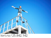 Купить «Young man in denim wear stands outstretching arms to sides on metal construction against blue sky», фото № 25842142, снято 12 июня 2015 г. (c) Losevsky Pavel / Фотобанк Лори