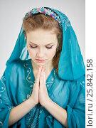 Купить «Closeup young woman in blue dress with hood prays», фото № 25842158, снято 7 марта 2015 г. (c) Losevsky Pavel / Фотобанк Лори