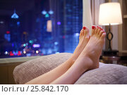 Купить «Woman puts her feet with red pedicure on pillow near window with city view», фото № 25842170, снято 5 ноября 2015 г. (c) Losevsky Pavel / Фотобанк Лори