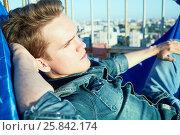 Купить «Closeup young man napping in hammock on building roof», фото № 25842174, снято 12 июня 2015 г. (c) Losevsky Pavel / Фотобанк Лори