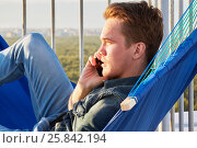 Купить «Closeup young man in denim clothes talks phone lying in hammock on building roof», фото № 25842194, снято 12 июня 2015 г. (c) Losevsky Pavel / Фотобанк Лори