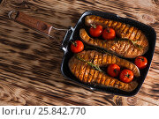 Aromatic steaks with spices cooked on a grill with tomatoes and rosemary. View from above. Стоковое фото, фотограф Татьяна Дубчук / Фотобанк Лори
