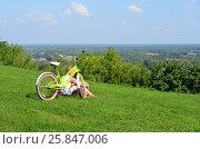 Купить «Девушка с велосипедом сидит на холме над рекой Клязьмой в городе Владимире», эксклюзивное фото № 25847006, снято 24 августа 2016 г. (c) Наталья Горкина / Фотобанк Лори