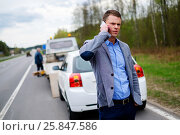 Купить «Man calling while tow truck picking up his broken car», фото № 25847586, снято 24 апреля 2018 г. (c) Andrejs Pidjass / Фотобанк Лори