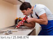 Купить «Young repairman working at the kitchen», фото № 25848874, снято 1 ноября 2016 г. (c) Elnur / Фотобанк Лори
