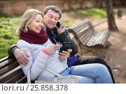 Купить «Middle-aged couple talking on the phone on a bench in the park in autumn», фото № 25858378, снято 23 марта 2016 г. (c) Татьяна Яцевич / Фотобанк Лори