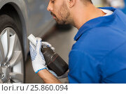 Купить «mechanic with screwdriver changing car tire», фото № 25860094, снято 1 июля 2016 г. (c) Syda Productions / Фотобанк Лори