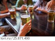 friends drinking beer at bar or pub. Стоковое фото, фотограф Syda Productions / Фотобанк Лори