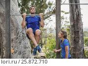 Купить «Fit man and woman performing pull-ups on bar during obstacle course», фото № 25872710, снято 24 ноября 2016 г. (c) Wavebreak Media / Фотобанк Лори