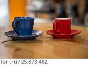 Купить «Coffee cups on wooden table in cafeteria», фото № 25873482, снято 12 октября 2016 г. (c) Wavebreak Media / Фотобанк Лори