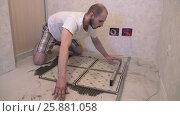 Worker aligns floor tiles on the floor. Стоковое видео, видеограф Кузьмов Пётр / Фотобанк Лори