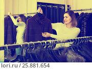 Купить «woman choosing sheepskin coat in women's cloths store», фото № 25881654, снято 7 июля 2020 г. (c) Яков Филимонов / Фотобанк Лори