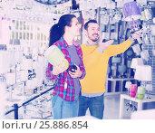 Купить «Couple is considering models of night lights», фото № 25886854, снято 16 февраля 2017 г. (c) Яков Филимонов / Фотобанк Лори