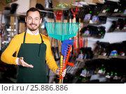 Купить «Seller displaying various items in garden equipment shop», фото № 25886886, снято 2 марта 2017 г. (c) Яков Филимонов / Фотобанк Лори