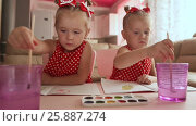 Купить «Two little sisters twins are happy to paint drawings with watercolors sitting at the table together», видеоролик № 25887274, снято 12 января 2017 г. (c) Mikhail Davidovich / Фотобанк Лори