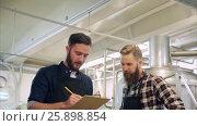 Купить «men with clipboard at brewery or beer plant», видеоролик № 25898854, снято 30 марта 2017 г. (c) Syda Productions / Фотобанк Лори