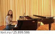 Купить «Young beautiful lady playing the piano and singing, posing for the camera», видеоролик № 25899586, снято 8 ноября 2016 г. (c) Mikhail Davidovich / Фотобанк Лори