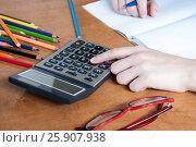 Купить «The student counts on calculator and writes in notebook», фото № 25907938, снято 2 апреля 2017 г. (c) Катерина Белякина / Фотобанк Лори