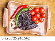 Pieces of beef jerky, tomatoes, hot pepper and spices on a wooden tray on a wooden table. Стоковое фото, фотограф Ольга Соловьева / Фотобанк Лори
