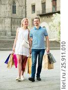 Купить «Couple looking satisfied after shopping in city», фото № 25911010, снято 19 сентября 2019 г. (c) Яков Филимонов / Фотобанк Лори