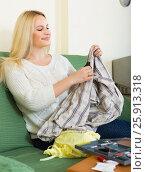 Купить «Housewife stitching tears of clothes», фото № 25913318, снято 17 августа 2018 г. (c) Яков Филимонов / Фотобанк Лори