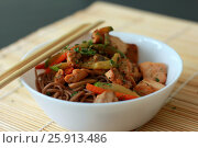 Гречневая лапша с рыбой, овощами, китайские палочки на кухонном столе. Стоковое фото, фотограф Галина Жигалова / Фотобанк Лори