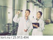 Купить «Man and woman employees on winery manufactory», фото № 25913494, снято 21 мая 2018 г. (c) Яков Филимонов / Фотобанк Лори