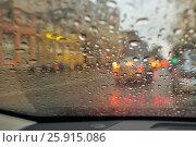 Купить «Вид городской улицы сквозь ветровое стекло автомобиля, покрытое каплями дождя», эксклюзивное фото № 25915086, снято 5 апреля 2017 г. (c) Александр Алексеев / Фотобанк Лори