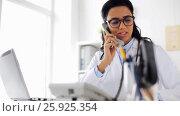 Купить «happy female doctor calling on phone at hospital», видеоролик № 25925354, снято 16 марта 2017 г. (c) Syda Productions / Фотобанк Лори