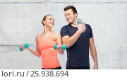 Купить «sportive man and woman with dumbbell and water», фото № 25938694, снято 2 марта 2017 г. (c) Syda Productions / Фотобанк Лори