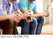 Купить «men with beer bottles sitting on sofa at home», фото № 25938710, снято 22 марта 2014 г. (c) Syda Productions / Фотобанк Лори