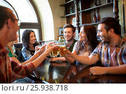 Купить «happy friends drinking beer at bar or pub», фото № 25938718, снято 14 июля 2016 г. (c) Syda Productions / Фотобанк Лори