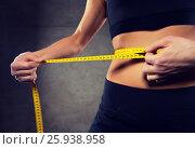 Купить «close up of woman measuring waist by tape in gym», фото № 25938958, снято 12 декабря 2015 г. (c) Syda Productions / Фотобанк Лори
