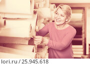 Купить «Mature female shopper searching for suitable fabric», фото № 25945618, снято 15 февраля 2017 г. (c) Яков Филимонов / Фотобанк Лори