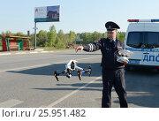 Купить «Инспектор дорожно-патрульной службы полиции контролирует трассу с помощью квадрокоптера», фото № 25951482, снято 14 мая 2016 г. (c) Free Wind / Фотобанк Лори