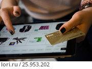 Купить «Moscow, Russia, 8 april 2017. Women hold visa gold card and use ipad for online shopping.», фото № 25953202, снято 8 апреля 2017 г. (c) Богданов Степан / Фотобанк Лори