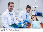 Купить «Dentist showing digital tablet to young patient», фото № 25969510, снято 11 декабря 2016 г. (c) Wavebreak Media / Фотобанк Лори