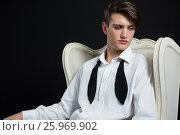 Купить «Androgynous man sitting on chair against black background», фото № 25969902, снято 15 декабря 2016 г. (c) Wavebreak Media / Фотобанк Лори