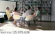 Купить «Young people in library», видеоролик № 25970638, снято 19 августа 2016 г. (c) Raev Denis / Фотобанк Лори